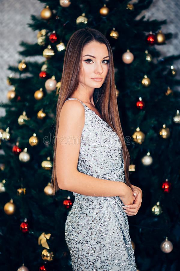 Party, drinks, holidays, luxury and celebration concept smiling woman in evening dress with glass of champagne over lights backgro stock image