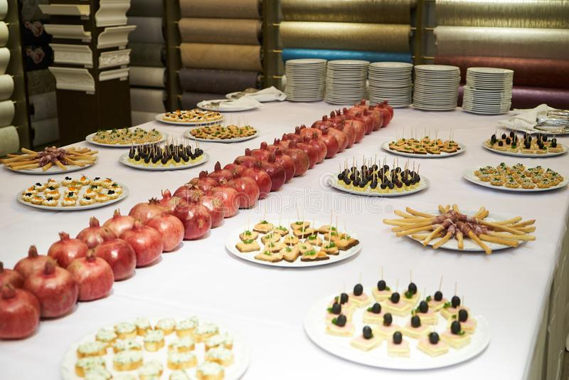 Party event buffet table with assortment of canapes and pomegranate. On table. Catering Fourchette table with sandwiches, snacks for wine, close-up stock image