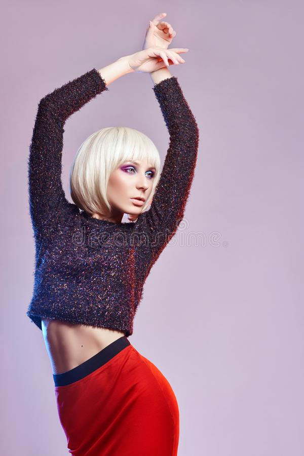 Party fashion Blonde woman in dark, shiny shirt and red long ski. Rt with bright, vivid makeup, white background with contrast coloured spots. Fashion makeup stock image