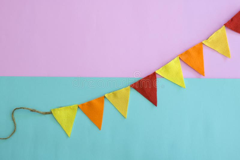 Party flags hanging on blue and pink background. royalty free stock image