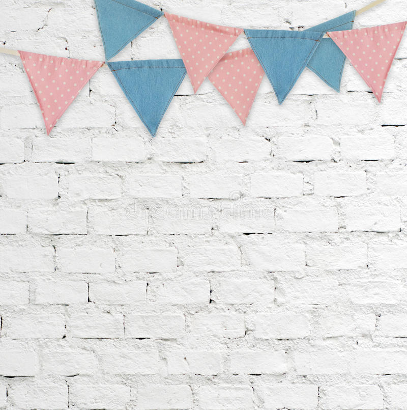 Party flags hanging on white brick wall background royalty free stock photography