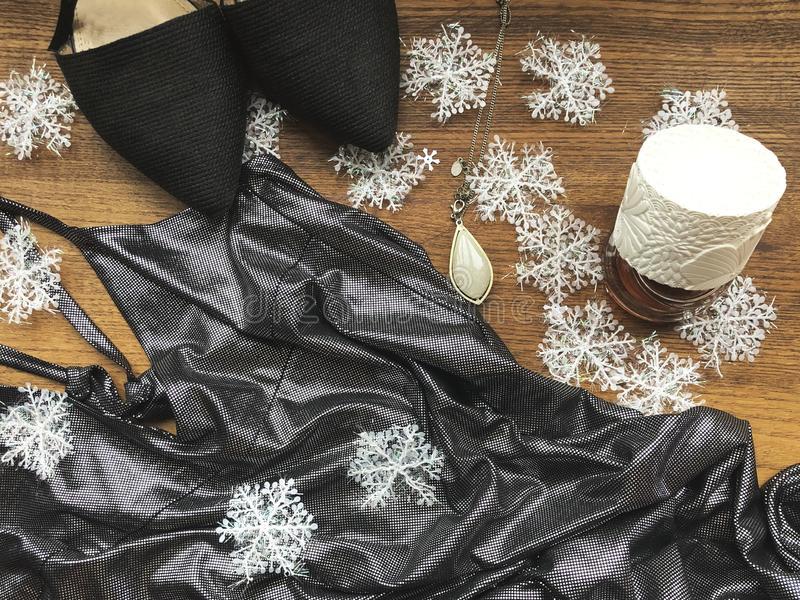 Party flat lay. New year party. Female silver dress, black shoes, perfume and necklace with snowflakes. Femal fashion flatlay. New stock photos
