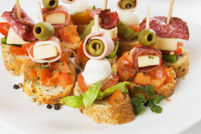Party food. Italian canape with prosciutto, olive, mozarella cheese and bruschetta bread royalty free stock image