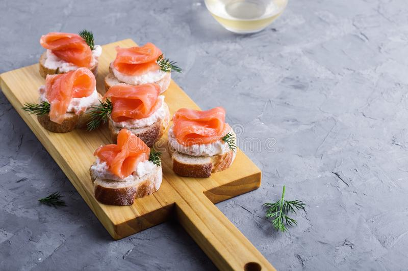 Party food, appetizer with salmon pate and smoked salmon on  cutting board. Party food, appetizer with salmon pate and smoked salmon on wooden cutting board stock photos