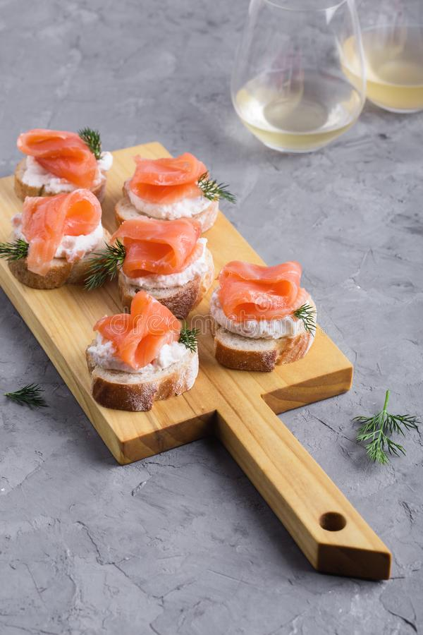 Party food, appetizer with salmon pate and smoked salmon on  cutting board. Party food, appetizer with salmon pate and smoked salmon on wooden cutting board stock images