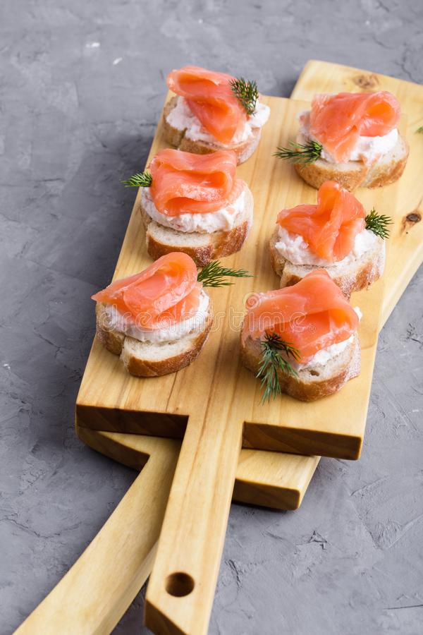 Party food, appetizer with salmon pate and smoked salmon on  cutting board. Party food, appetizer with salmon pate and smoked salmon on wooden cutting board royalty free stock photos