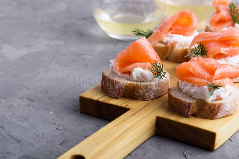 Party food, appetizer with salmon pate and smoked salmon on  cutting board. Party food, appetizer with salmon pate and smoked salmon on wooden cutting board stock photography