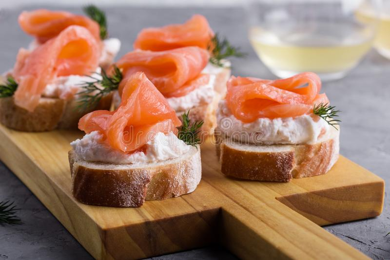 Party food, appetizer with salmon pate and smoked salmon on  cutting board. Party food, appetizer with salmon pate and smoked salmon on wooden cutting board royalty free stock photography