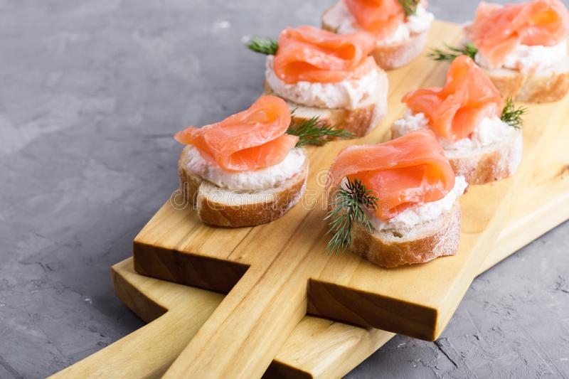 Party food, appetizer with salmon pate and smoked salmon on  cutting board. Party food, appetizer with salmon pate and smoked salmon on wooden cutting board royalty free stock image