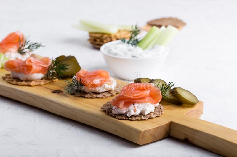 Party food, appetizer with salmon pate and smoked salmon on  cutting board. Party food, appetizer with salmon pate and smoked salmon, yoghurt dip with dill royalty free stock photos