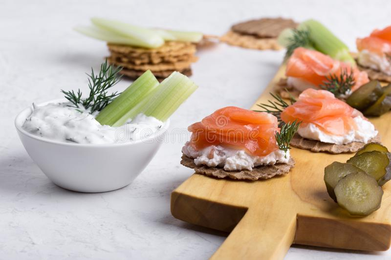 Party food, appetizer with salmon pate and smoked salmon on  cutting board. Party food, appetizer with salmon pate and smoked salmon, yoghurt dip with dill stock photography