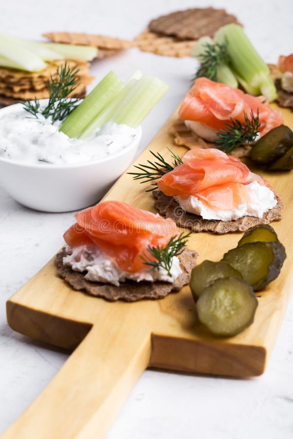 Party food, appetizer with salmon pate and smoked salmon on  cutting board. Party food, appetizer with salmon pate and smoked salmon, yoghurt dip with dill stock images