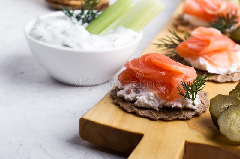 Party food, appetizer with salmon pate and smoked salmon on  cutting board. Party food, appetizer with salmon pate and smoked salmon, yoghurt dip with dill royalty free stock images