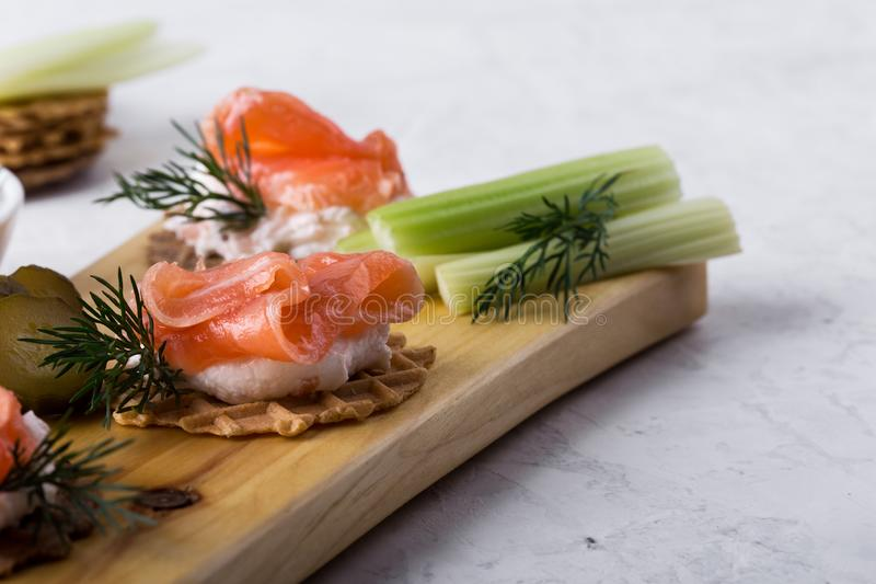 Party food, appetizer with salmon pate and smoked salmon on  cutting board. Party food, appetizer with salmon pate and smoked salmon, yoghurt dip with dill royalty free stock photography