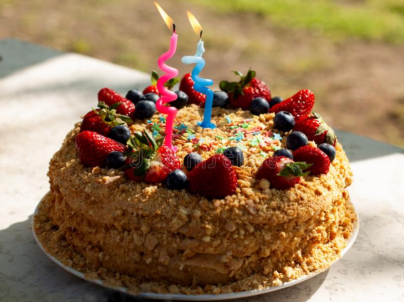 Party food concept. Homemade cake for Birthday decorated with candles, fresh blueberries, strawberries. Two years old. stock images