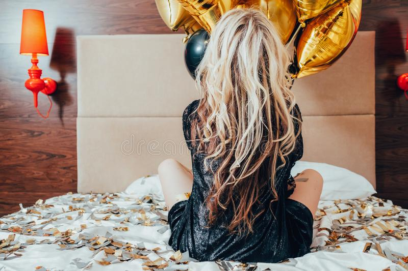 Party free alone female bed confetti balloons. Party over. Free alone. Blonde female sitting on bed scattered with confetti. Balloons in hands. Memories and stock image