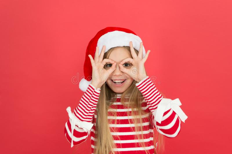 Party fun. Happy kid make glasses gesture red background. Little girl enjoy santa claus party. New Year Eve party. Join royalty free stock image