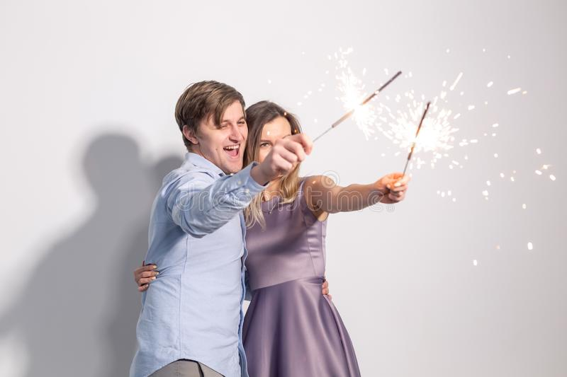 Party, fun and holidays concept - young happy couple with sparklers on white background stock photos
