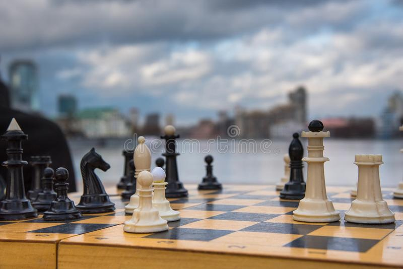 Party game white and black chess pieces on a wooden board against the backdrop of a city and sky with clouds. Party game white and black chess pieces on a wooden stock photos