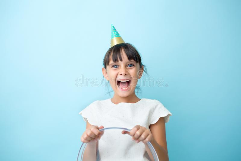 Happy kid with a party cone hat. Party girl with a big smile royalty free stock images