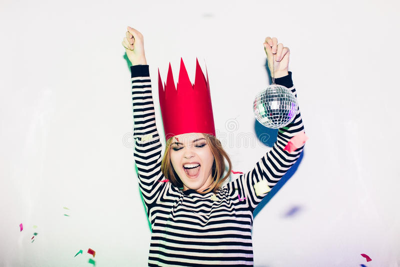 Party girl in colorful spotlights and confetti smiling on white background celebrating brightful event, wears stripped stock photography