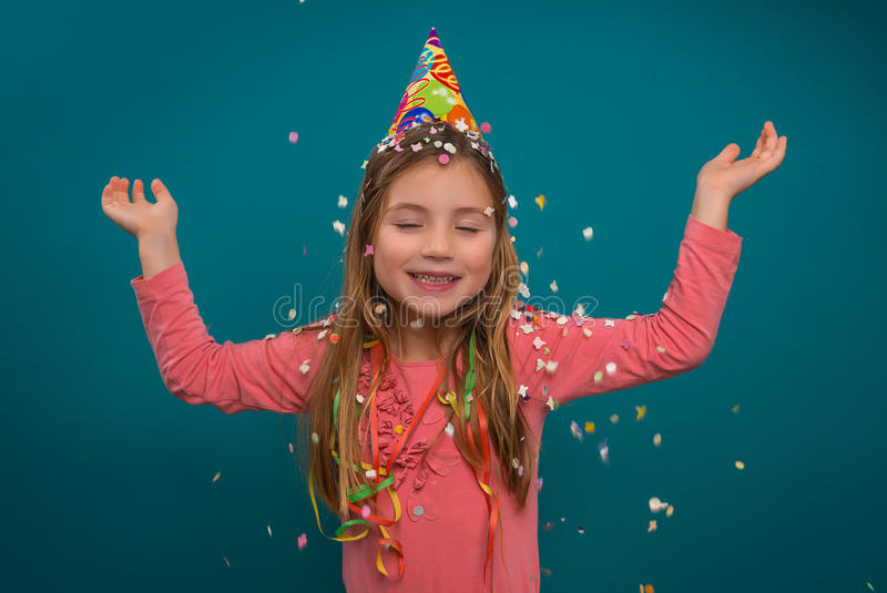 Party girl with confetti. Little cute girl celebratin new year party royalty free stock photo