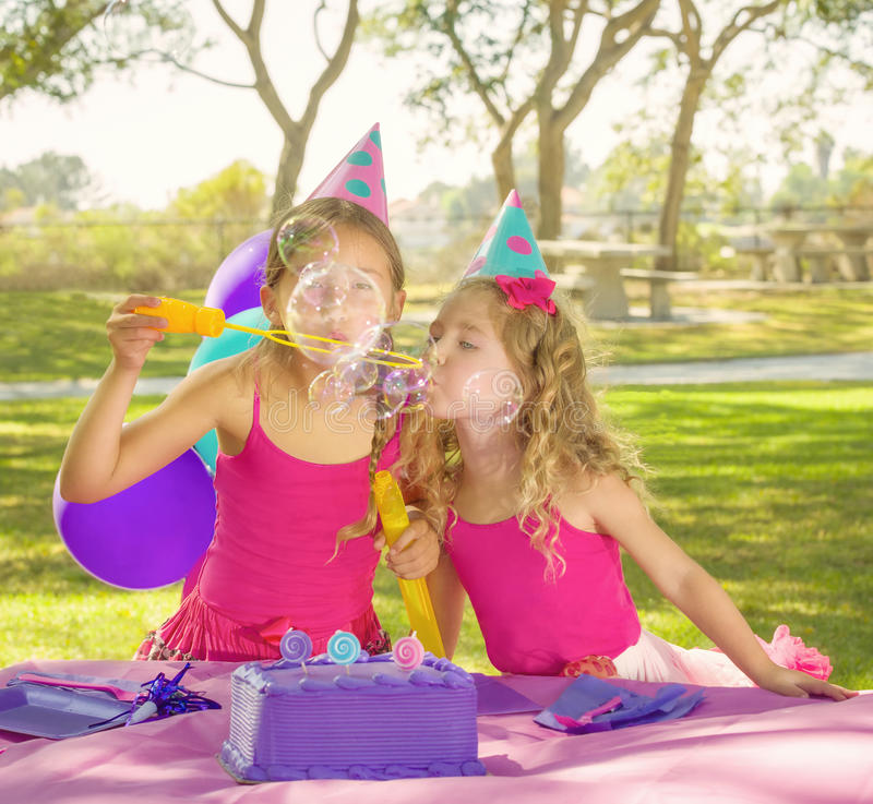 Party Girls Blowing Bubbles. Two girls, sisters, wearing party hats and getting ready to eat cake, blow bubbles for fun at a birthday party in a neighborhood