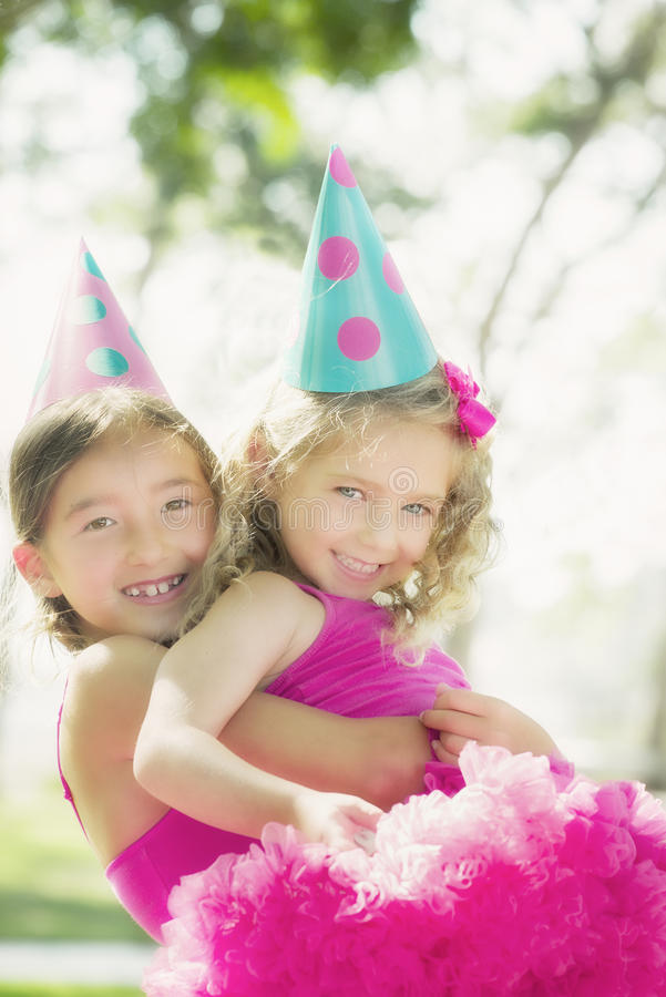 Party Girls. Two smiling girls in party hats, sisters, have fun at a birthday party, with one sister holding and lifting the other