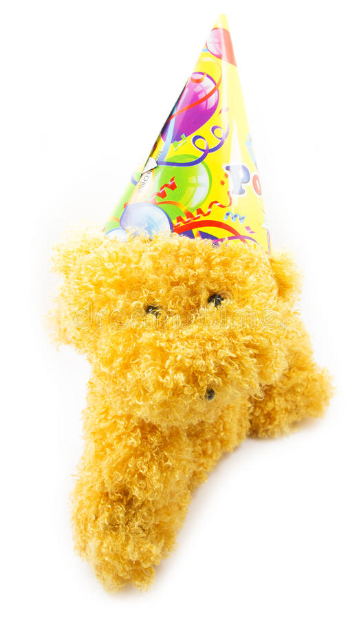 Party handmade toy on a white background. Birthday toy, golden dog, fluffy toy, patry toy with festive cap, festive cap on a handmade toy, white background royalty free stock photos