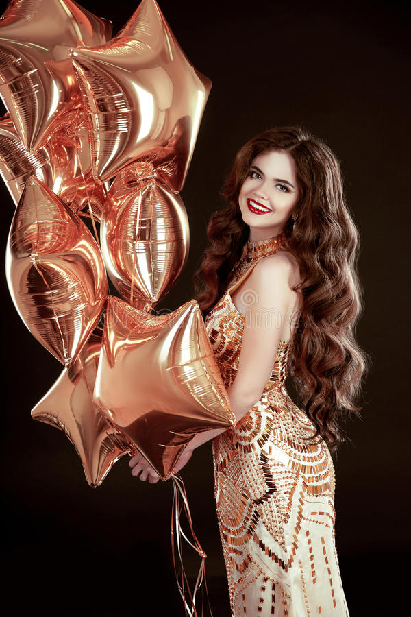 Party. Happy brunette girl with golden star balloons wears in elegant dress isolated on black studio background. Holiday, birthday concept royalty free stock photo