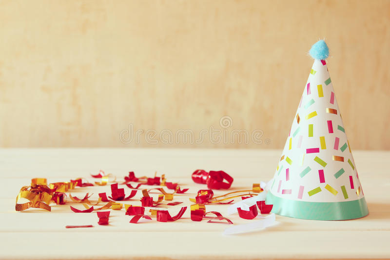 Download Party Hat Next To Colorful Confetti On Wooden Table. Stock Photo - Image of party, carnival: 74139416