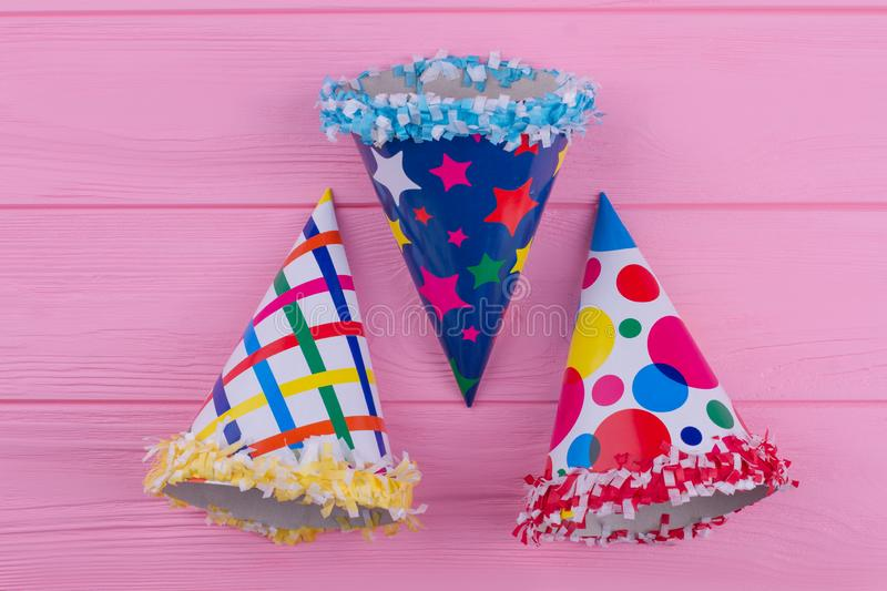 Party hats set on pink background. New Years Eve or Birthday caps on color wooden background royalty free stock images