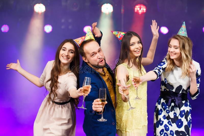 Party, holidays, celebration, nightlife and people concept - smiling friends with glasses of champagne in club. stock photo