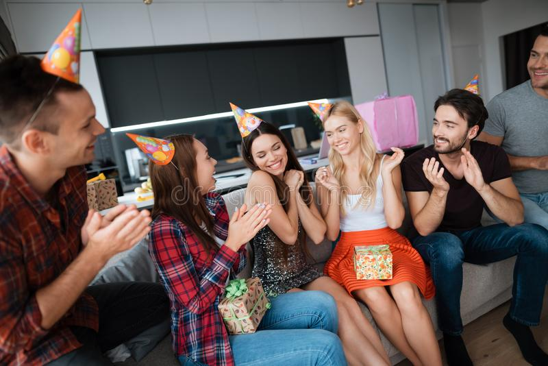 Party in honor of the birthday. Guests give their gifts to the birthday girl. The girl is very happy to receive gifts. royalty free stock image