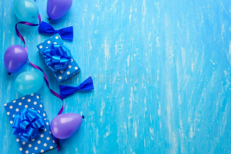 Party invitation card template. Violet and baby-blue balloons, paper bows, gift boxes, ribbons along the left edge. Place to insert your text on the blue royalty free stock photo