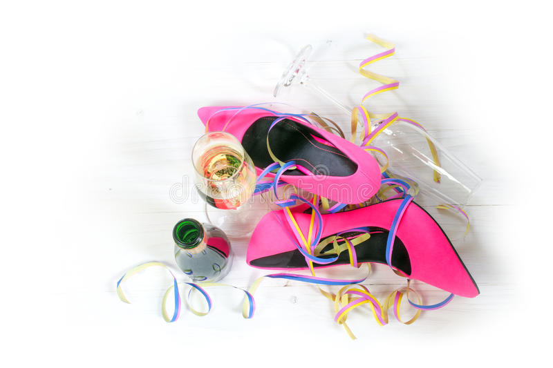 After the party, ladies pink high heels shoes lying on the floor. Streamers, champagne glasses and bottle from a happy women's day, view from above, background stock photo