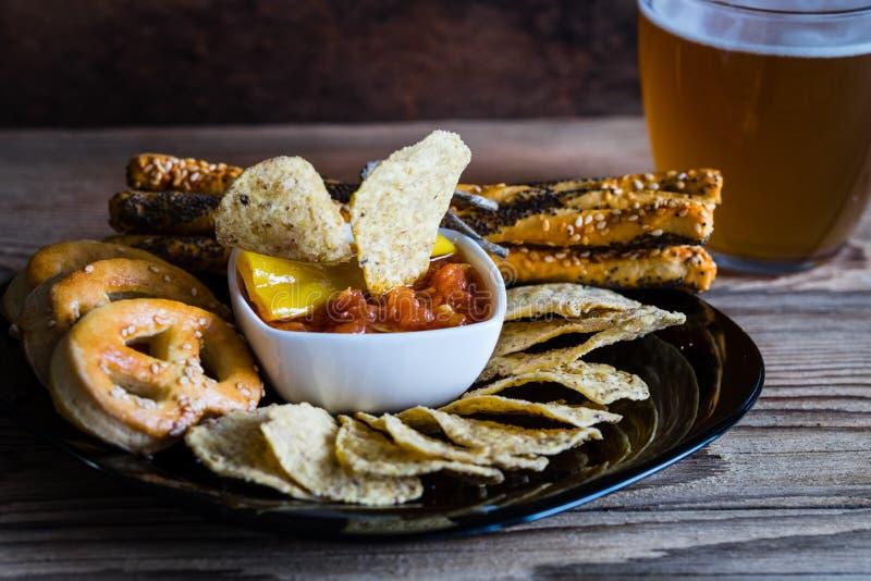 Party microplaquetas de tortilha da mistura, pilha de varas de pão e pretzeis e vidro da cerveja foto de stock royalty free