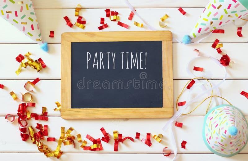 Party o chapéu ao lado dos confetes coloridos e do quadro-negro vazio fotos de stock royalty free