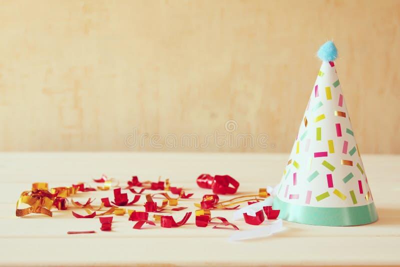 Party o chapéu ao lado dos confetes coloridos na tabela de madeira imagem de stock royalty free