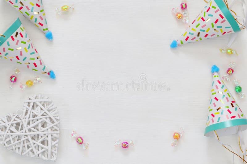 Party o chapéu ao lado dos confetes coloridos na tabela de madeira imagens de stock