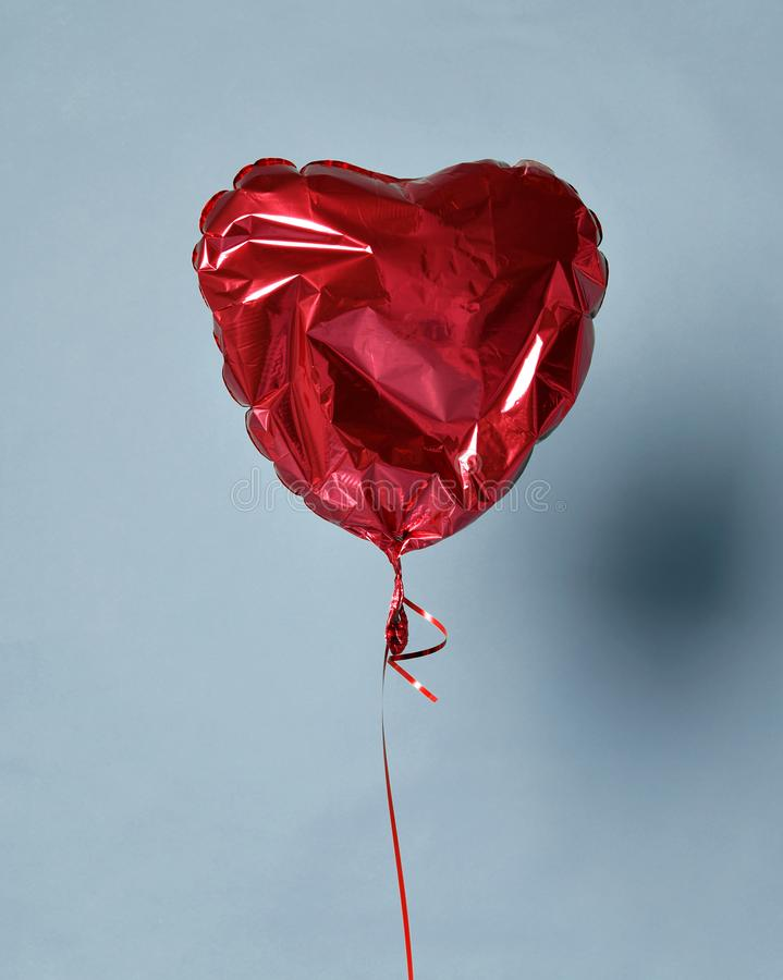 Party is over deflated red heart balloon object for birthday party or love valentines day stock photo