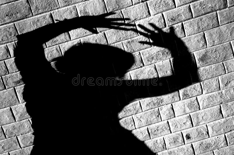 Party people. Shadow of a woman dancing wildly with a white brick wall as a 'film noir' backdrop royalty free stock image