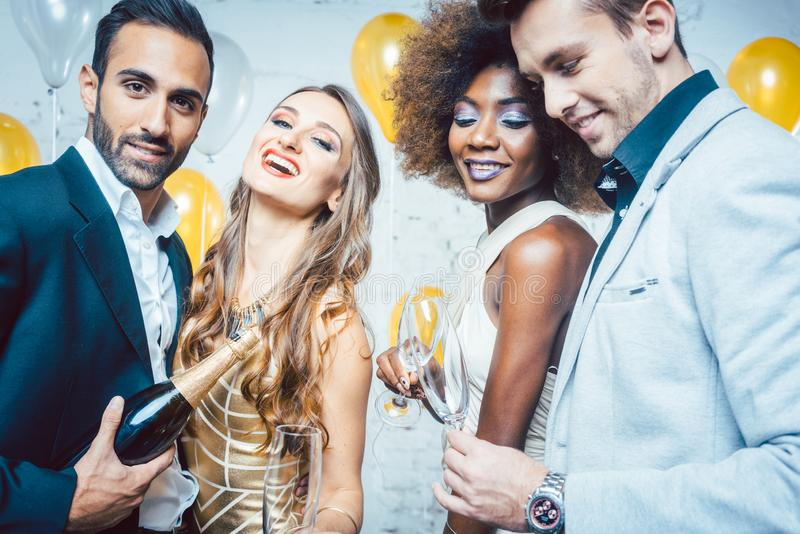 Party people in a club celebrating and pouring champagne royalty free stock photo
