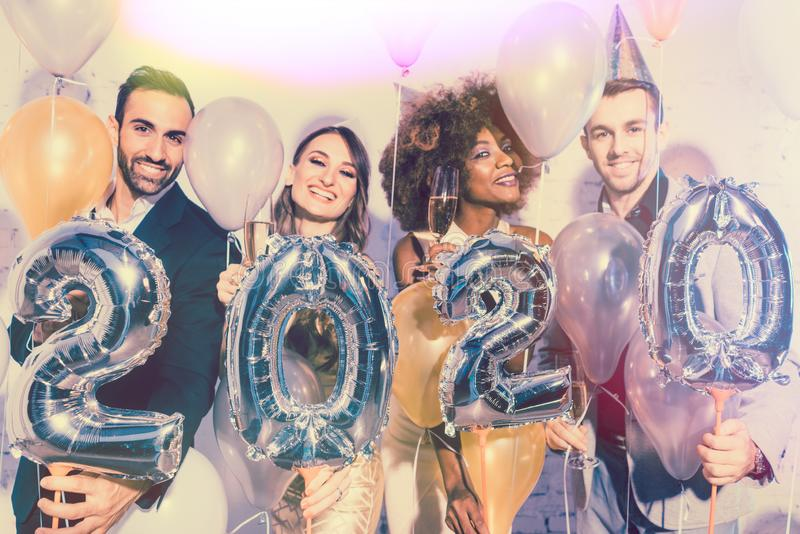 Party people women and men celebrating new years eve 2020 stock photography