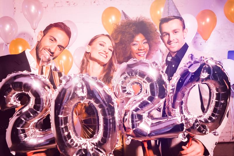 Party people women and men celebrating new years eve 2020 stock photos