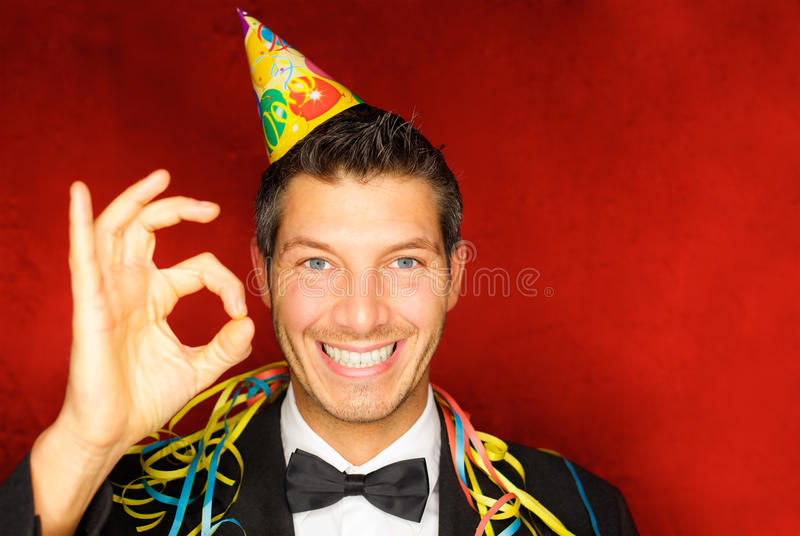 Party person celebrate new year. Happy smiling new years eve celebrating man with hat on party