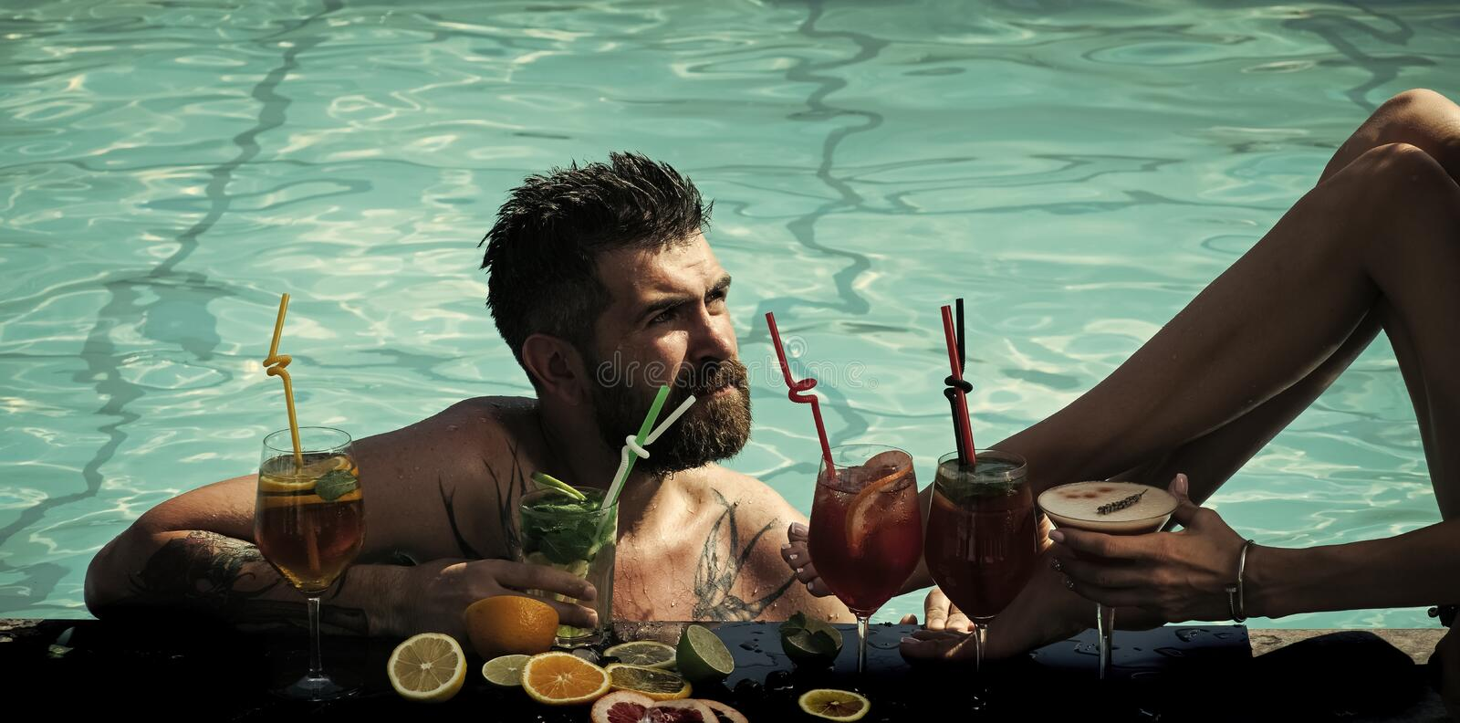 Party at the pool. Cocktail and bearded man in pool. royalty free stock image