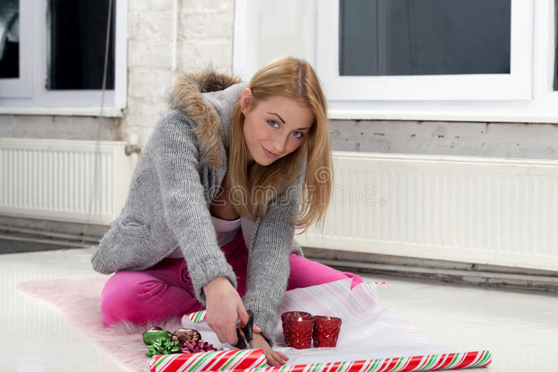 Party preparations. Girl with scissors preparing gifts for party stock image