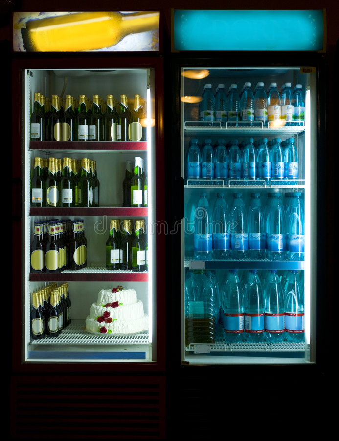 Party is ready. Two refrigerators glowing in the dark, loaded with beer, water and a birthday cake, ready for party night royalty free stock photo