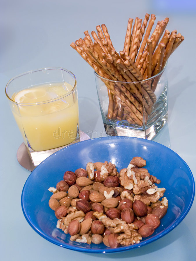 Party snacks. A bowl of nuts, glasses with orange alcoholic drink and salt sticks royalty free stock photos